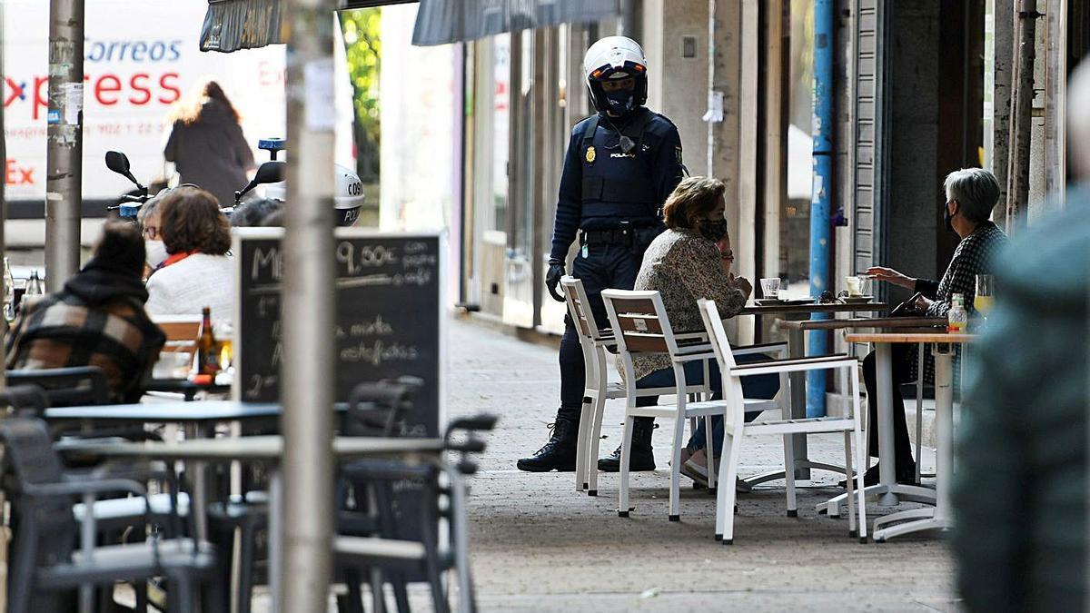 Un agente vigila que se cumplan las nuevas limitaciones en una terraza de Pontevedra. |   // GUSTAVO SANTOS