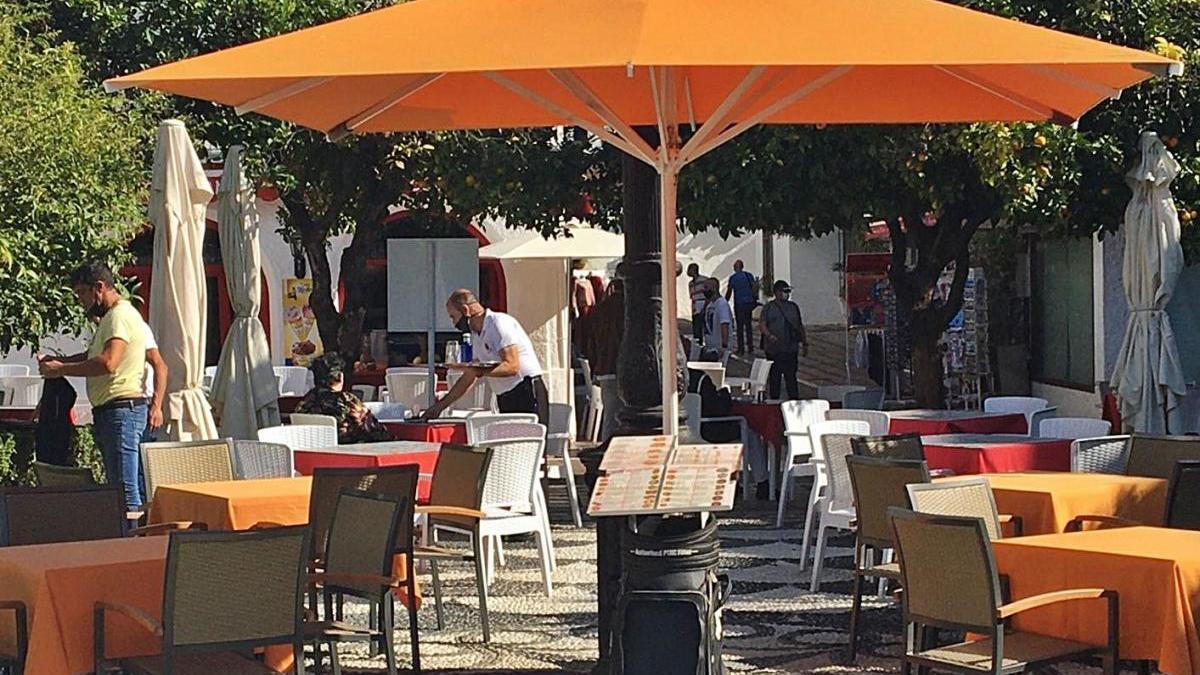 Un camarero atiende en una mesa ubicada en la plaza de Los Naranjos.