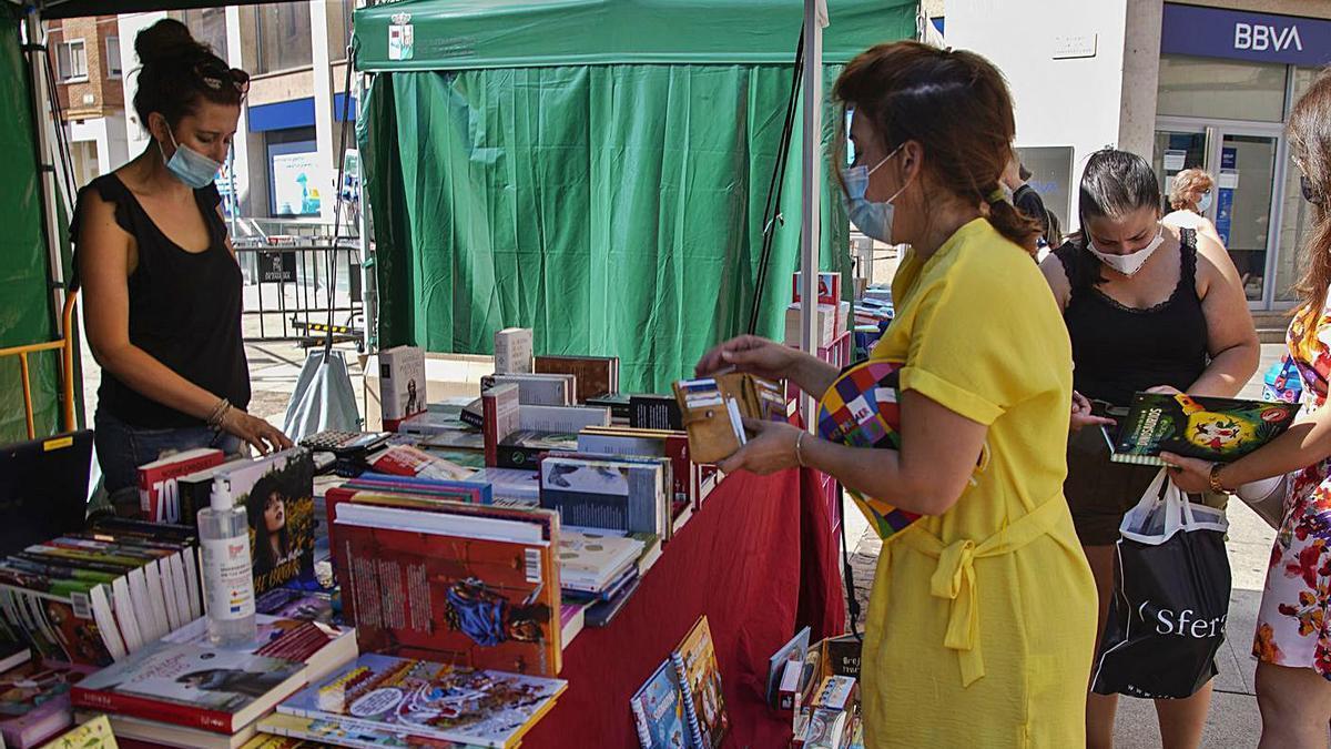 Una mujer compra un libro en uno de los puestos instalados en la plaza de la Constitución. | Jose Luis Fernández