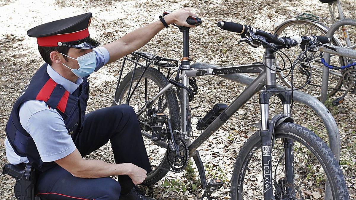 L'agent dels Mossos Sergi Jaén comprovant el número de bastidor d'una bici a Girona.   ANIOL RESCLOSA