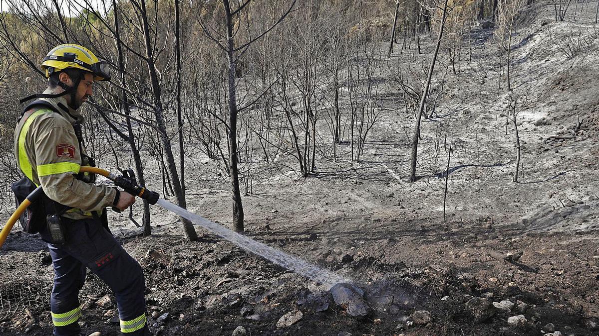 Un bomber remullant la superfície cremada en el foc de Ventalló. | ANIOL RESCLOSA