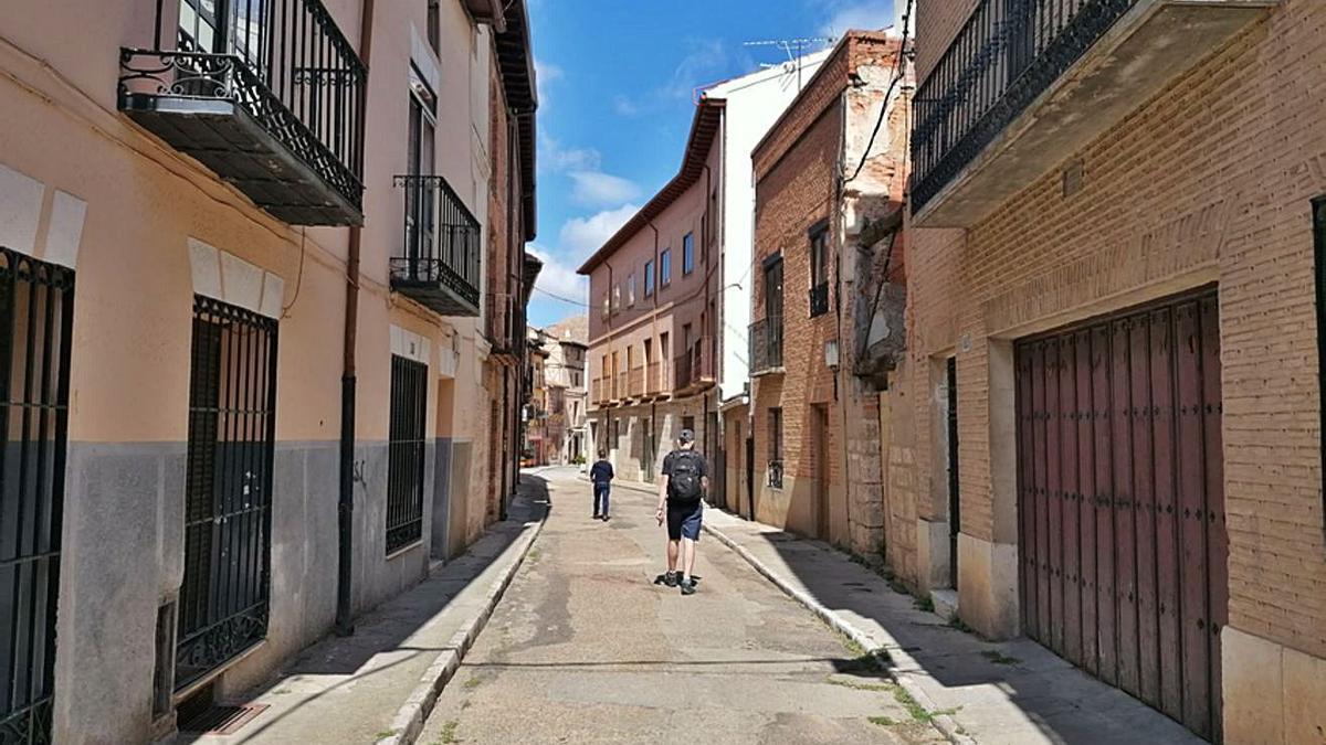 Vecinos pasean por la calle Candeleros en la que está previsto acometer obras de mejora. | M. J. C.