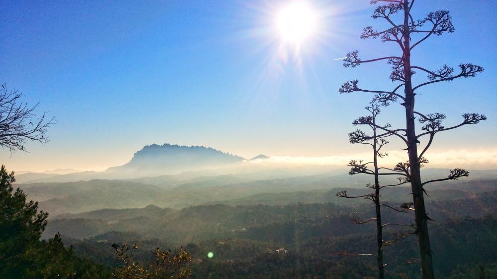 Castellfollit del Boix. Un dia assolellat des de Castellfollit del Boix, des d'on podem veure un camí de muntanyetes que ens guia per arribar a Montserrat, que es pot veure de fons amb un sol lluent.