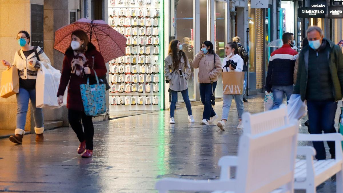 Varias personas pasean con mascarilla por una calle comercial.