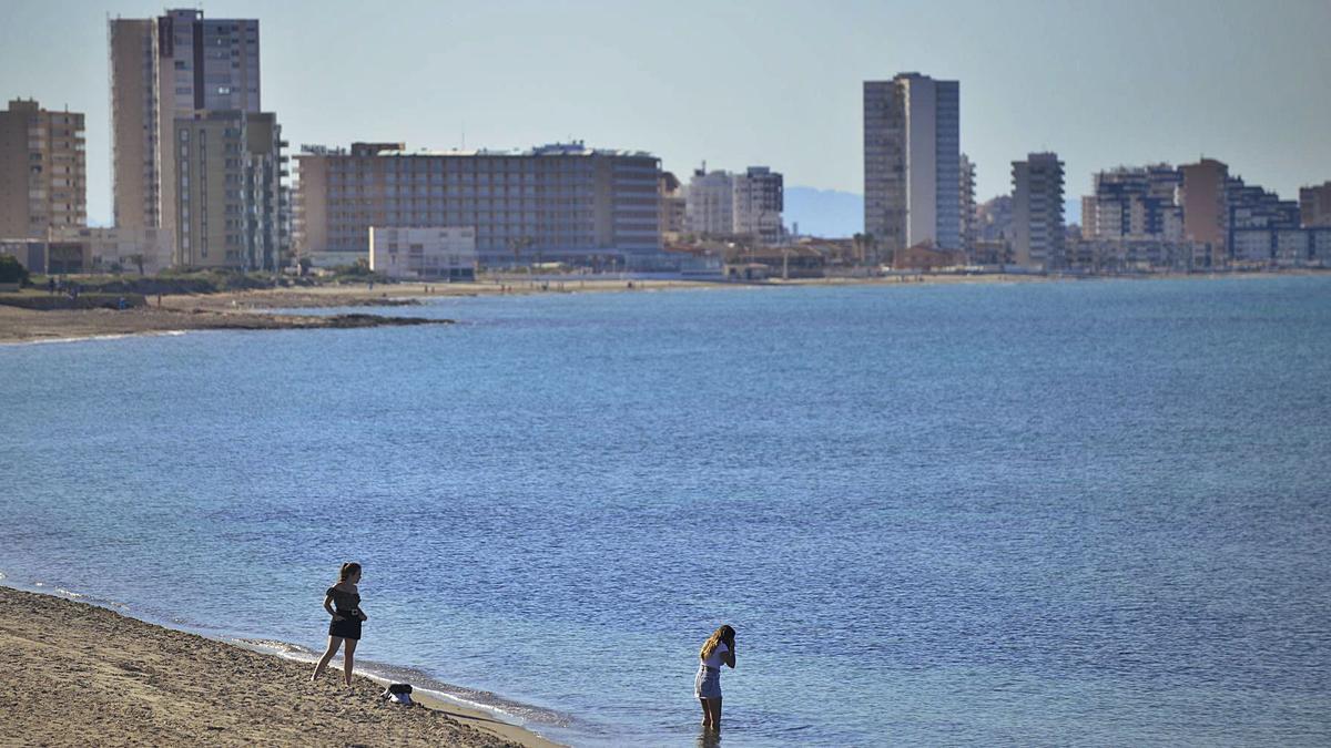 Dos jóvenes, a orillas de la playa de Levante de Cabo de Palos, que se adentra en el Mar Mediterráneo. | IVÁN URQUÍZAR