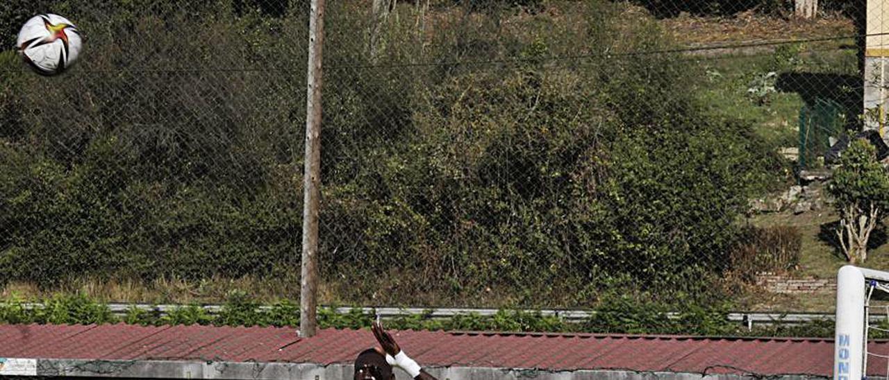 Saha salta para despejar de cabeza en un córner en el Llanera-Avilés. | F. R.