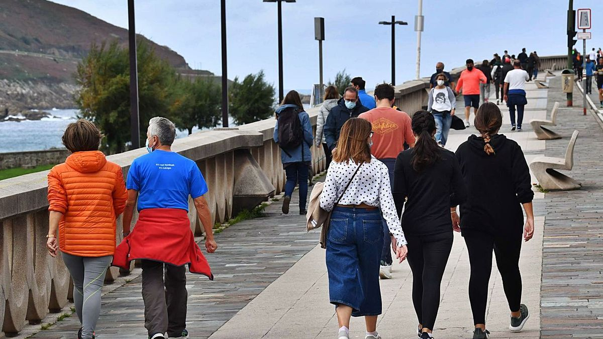 Ciudadanos caminan por el paseo marítimo de A Coruña.   | // VÍCTOR ECHAVE