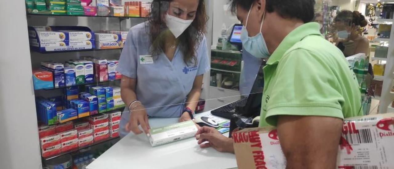 A la izquierda, Estefanía vende un autotest COVID. A la derecha, los diferentes tipos de pruebas que se pueden obtener en el establecimiento   LEVANTE-EMV