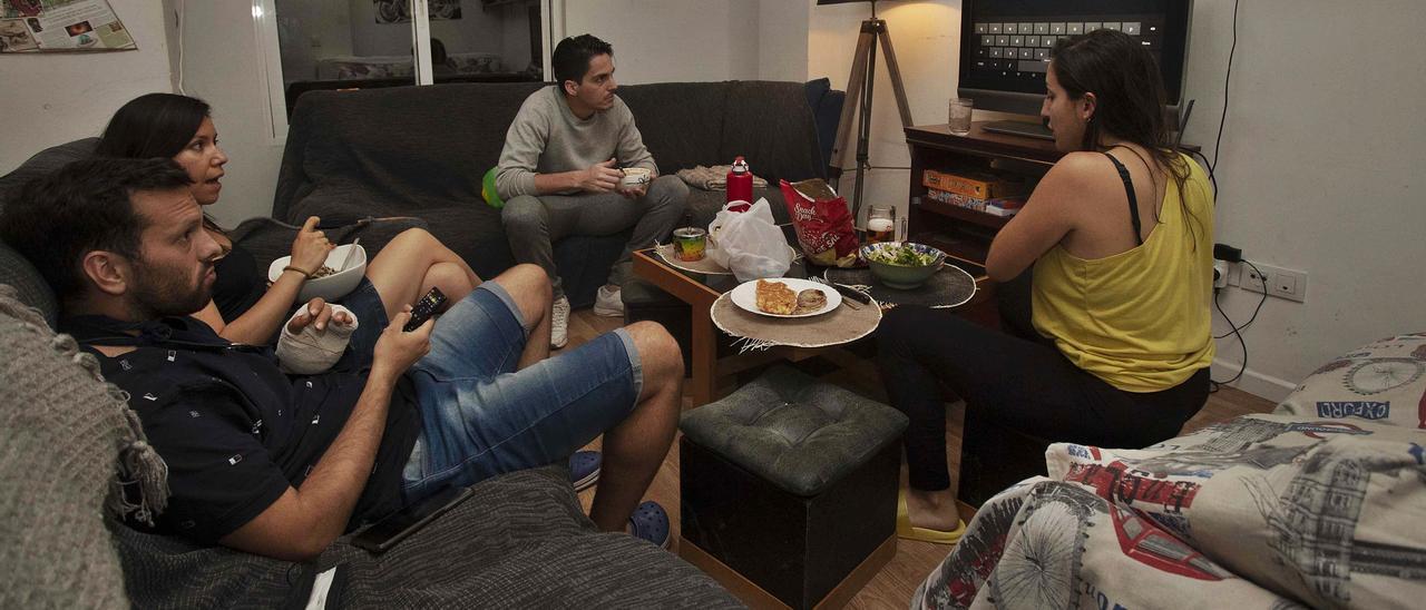 Elizabeth, Marina, Julio y Mauro, en el piso  que comparten en València, mientras   deciden qué ver en la televisión al término  de sus jornadas laborales. JM LÓPEZ
