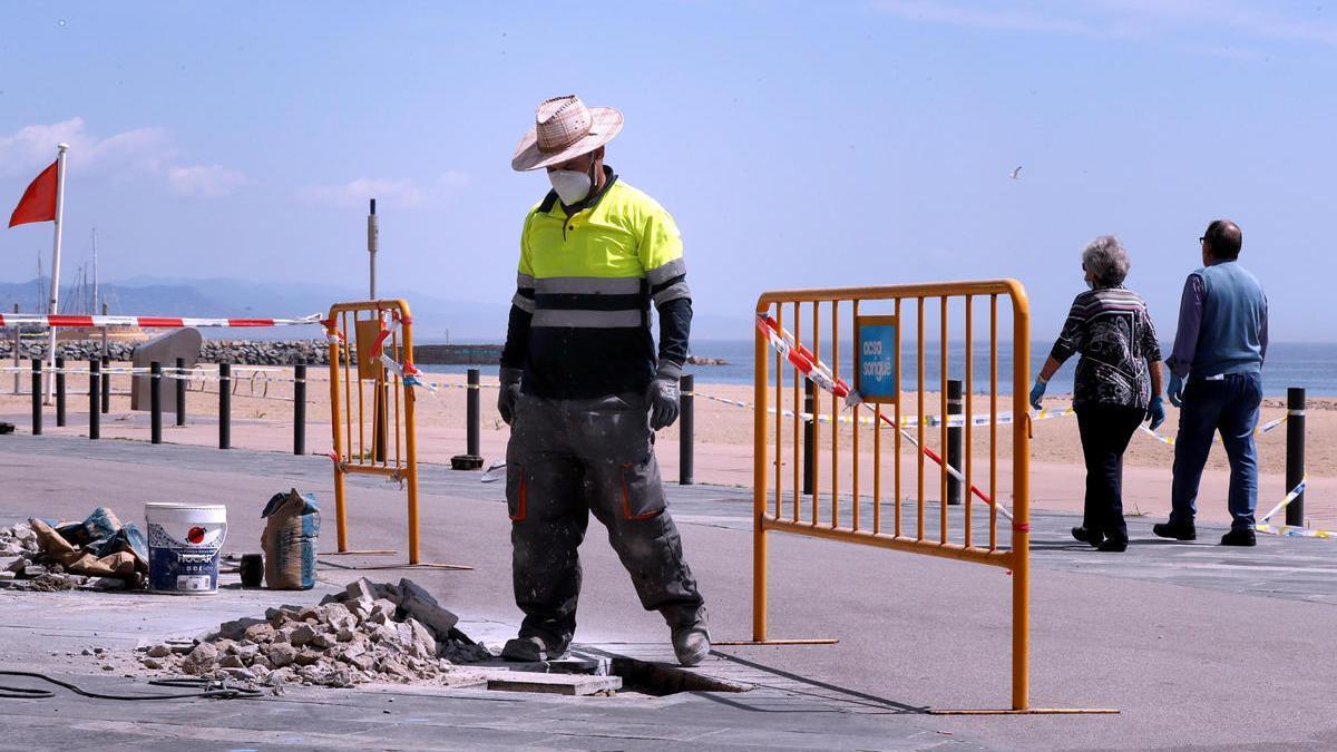 Un operario trabaja en la playa de Barcelona.