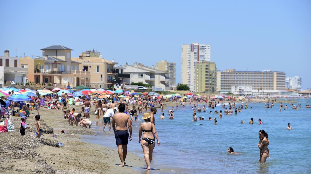 Bañistas disfrutan de una playa de La Manga en el primer día del verano.