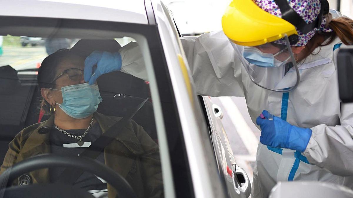 Una mujer se somete a una prueba PCR en un 'Coviauto' de A Coruña.     // CARLOS PARDELLAS
