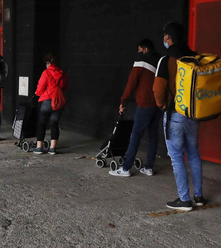 Dos repartidores guardan cola para el reparto que realiza el Banco  de Alimentos de València junto a las bolsas isotérmicas con las  que trabajan. josé manuel lópez