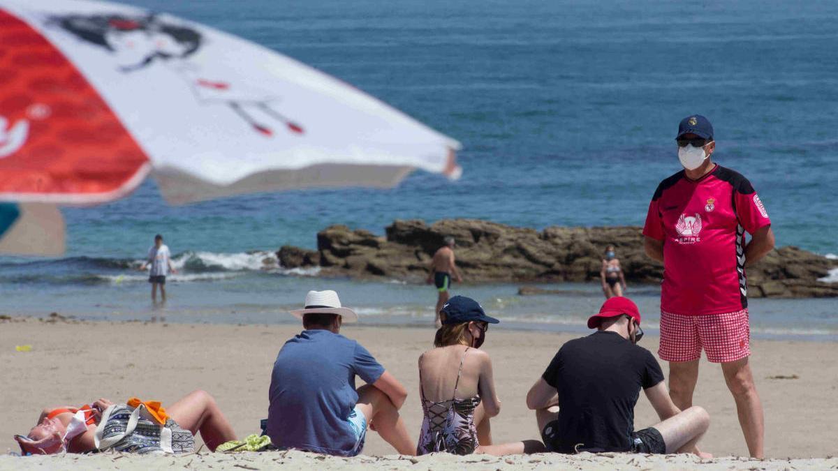 Bañistas con mascarilla en una playa de A Mariña. // EP
