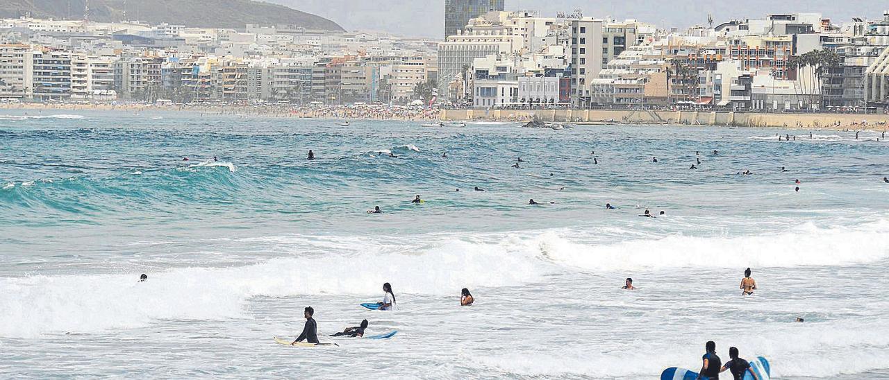 Varias personas cogen olas en la zona de La Cícer, en la playa de Las Canteras.