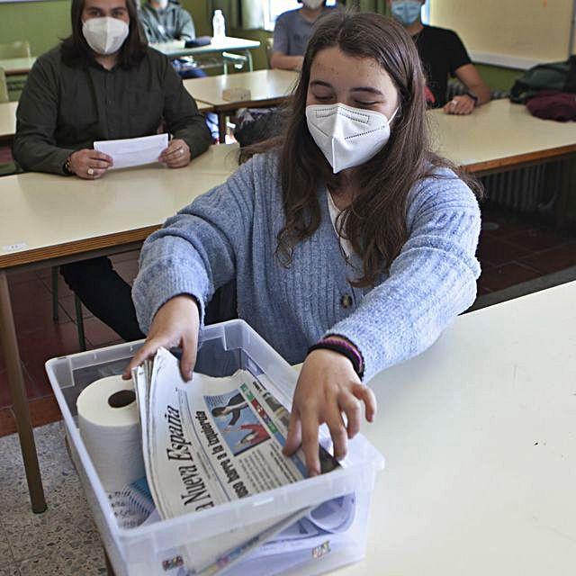 Una alumna deposita un exemplar de LA NUEVA ESPAÑA na cápsula del tiempu.