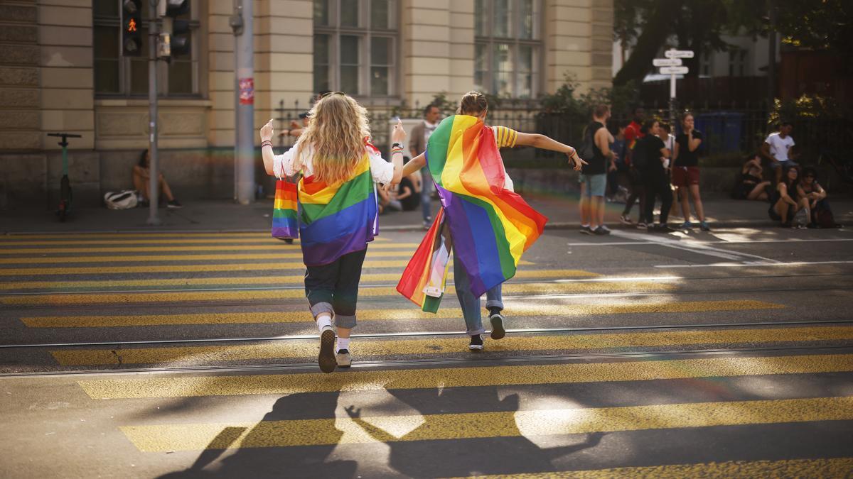Dos manifestantes portan banderas LGBTI en Zúrich.