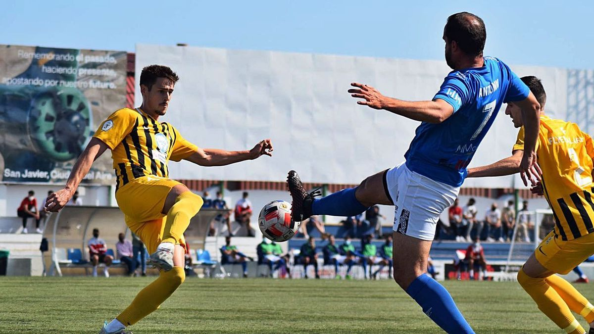 Antonio pugna por un rival por la posesión del balón.