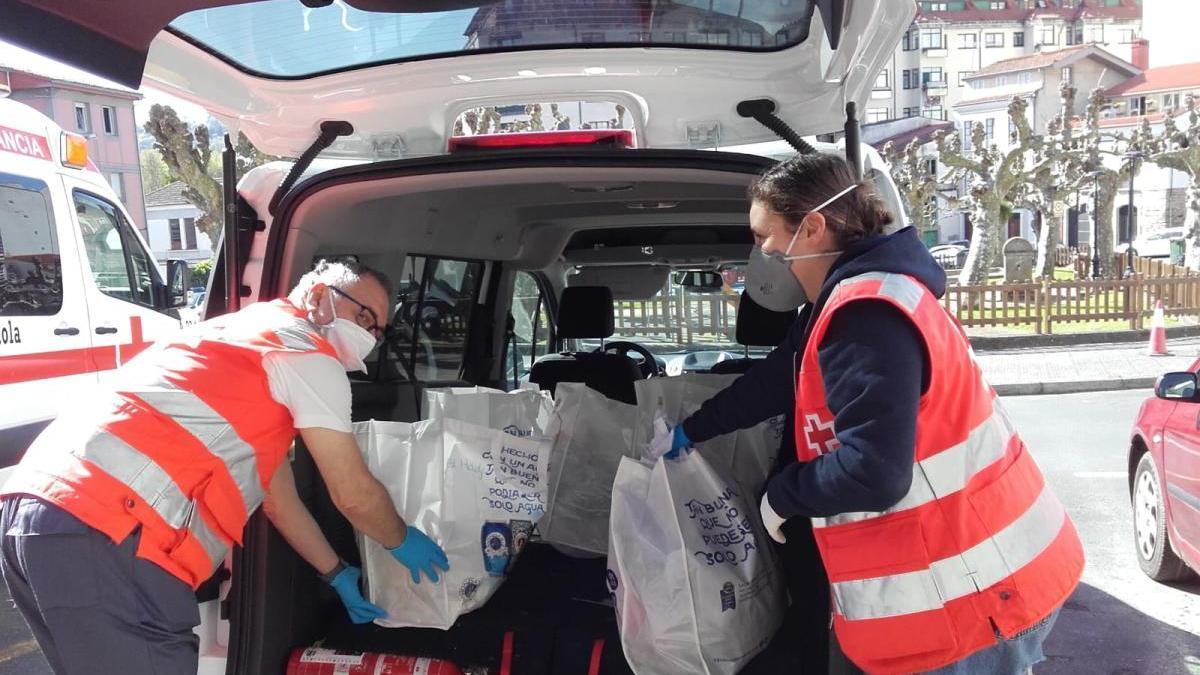 Dos integrantes de Cruz Roja de Betanzos durante un reparto de alimentos