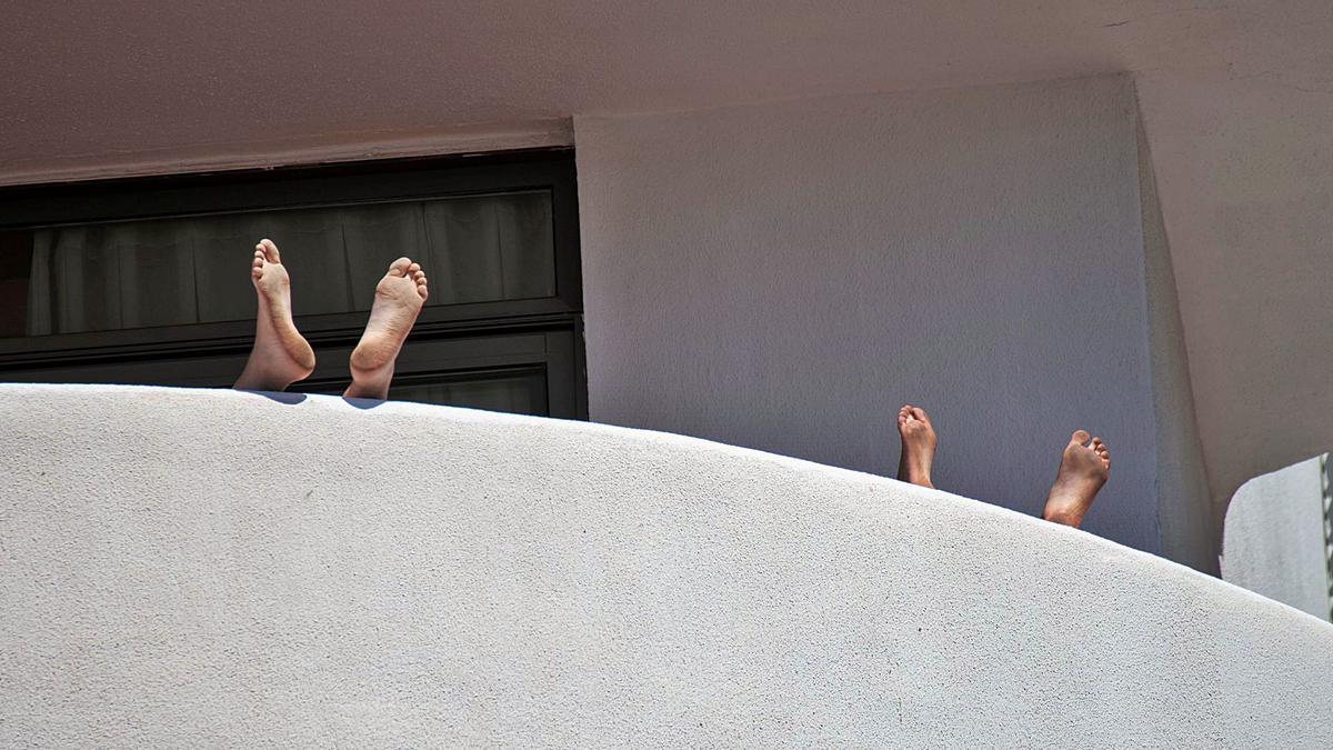 Dos estudiantes alojados en el hotel Palma Bellver del paseo Marítimo se relajan en la terraza de su habitación.