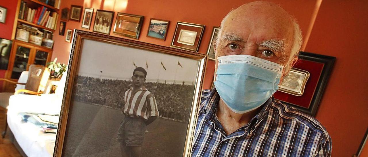 Armando Medina posa para LA NUEVA ESPAÑA en su domicilio con una foto en la que aparece en uno de sus  primeros partidos como jugador del Sporting. | Ángel González