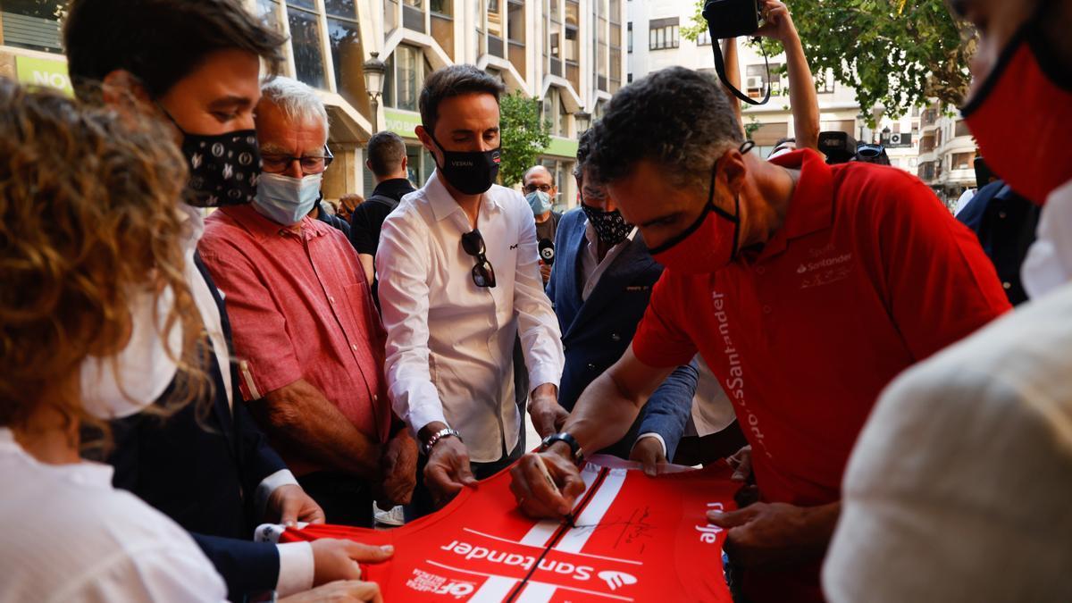 Induráin firma una camiseta ante Joan Ribó y Samuel Sánchez