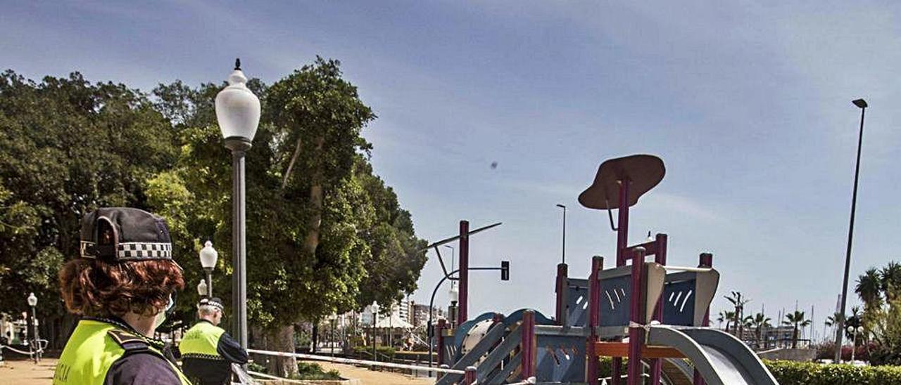 Una policía local renueva el precinto de un parque infantil de Alicante.