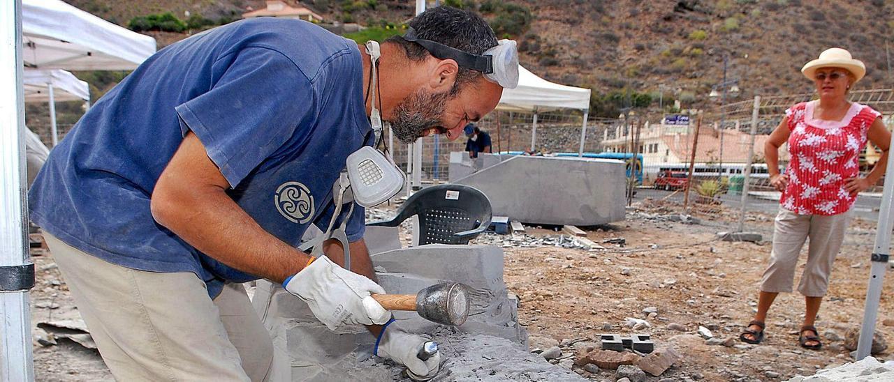 El escultor Fran Celis hace arte con piedra de Arucas durante el pasado bicentenario de Mogán.