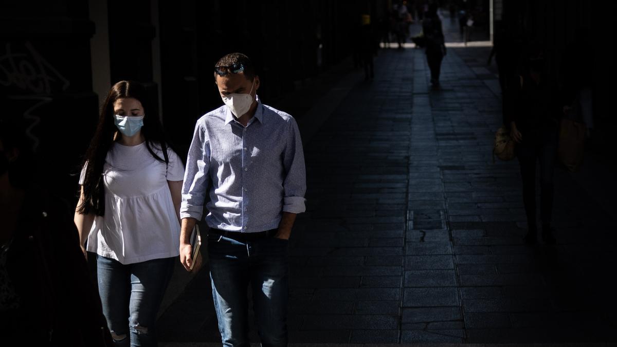 Dos personas pasean por una calle chicharrera.