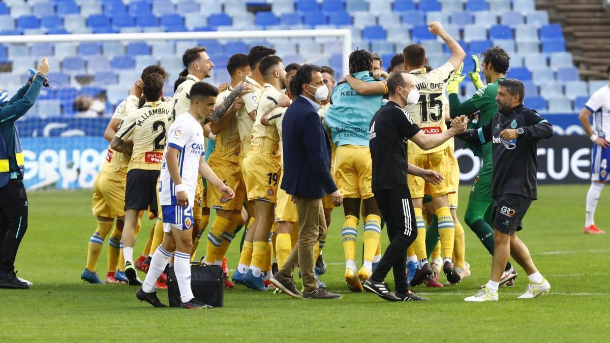 Bermejo, con gesto preocupado, pasa por delante de la piña del Espanyol, que celebra el ascenso.