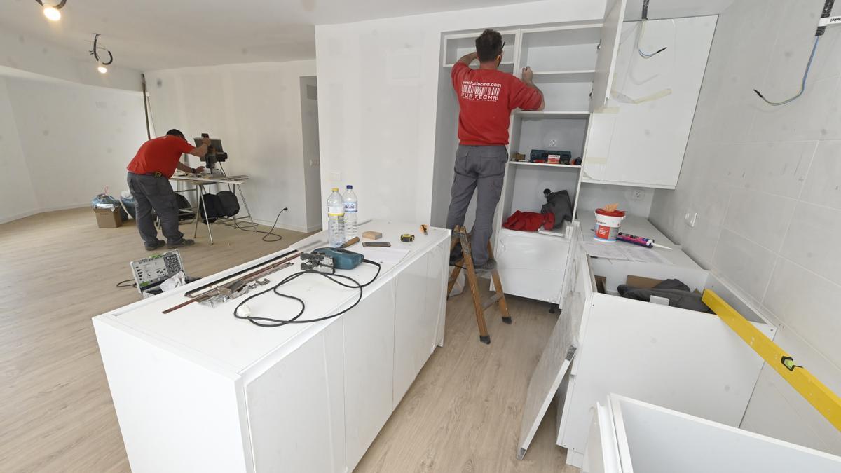 Unos operarios especialistas en el área de las reformas trabajan en la renovación de una cocina una vivienda.
