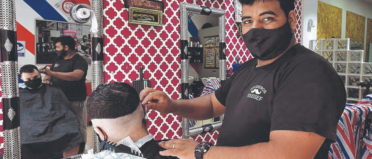 Youssef Rami corta el pelo a un cliente en su peluquería.