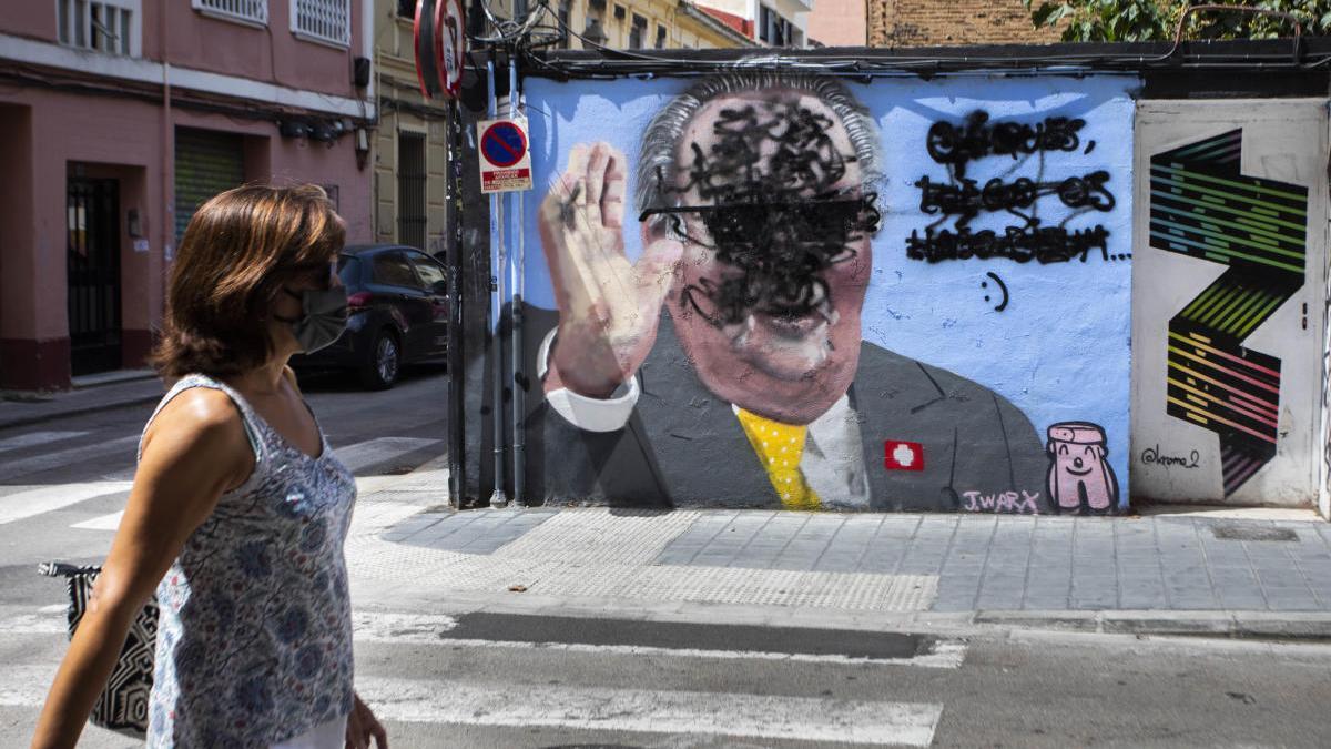 Un encapuchado tacha el mural satírico de Juan Carlos I en Benimaclet.