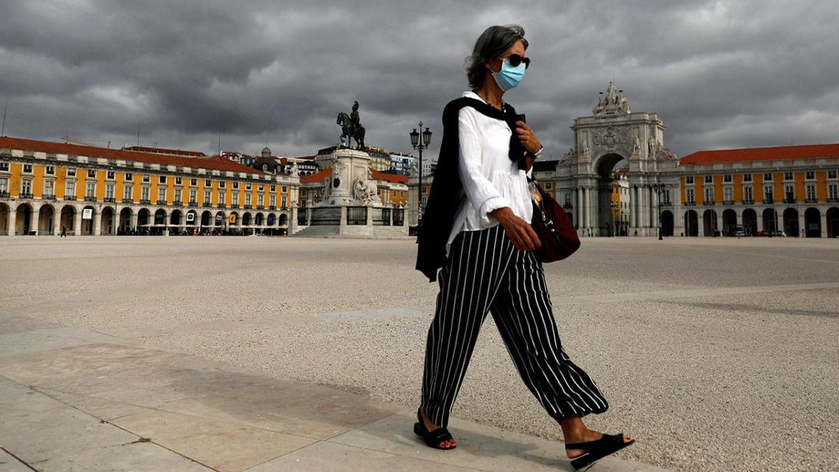 Una mujer con mascarilla cruza la Plaza del Comerciio en Lisboa
