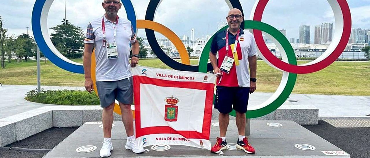 Carlos María Prendes (a la izquierda) y Marcelino Torrontegui, con la bandera del municipio de Carreño, en la Villa Olímpica de Tokio. | R. B. G.