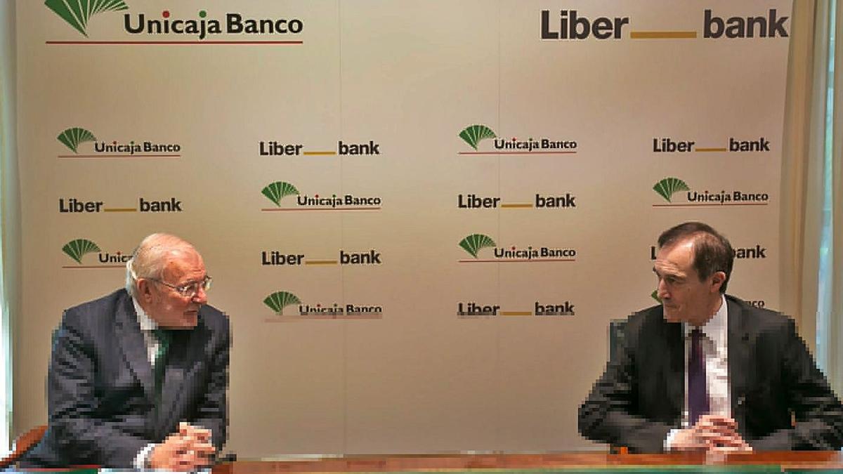 Azuaga, presidente de Unicaja Banco, y Menéndez, consejero delegado de Liberbank, durante la firma. | Ical