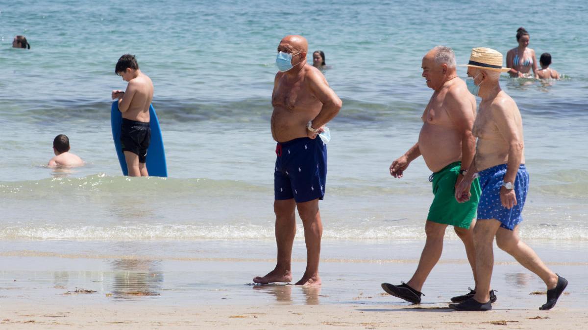 Bañistas con mascarilla en Foz. // EP