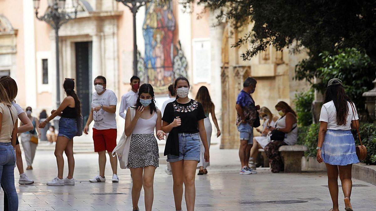 Dos chicas jóvenes caminan por el centro de València con la mascarilla puesta.