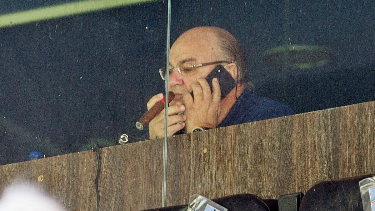 Juan Carlos Ramírez conversa y fuma mientras contempla el Hércules-Peña Deportiva.