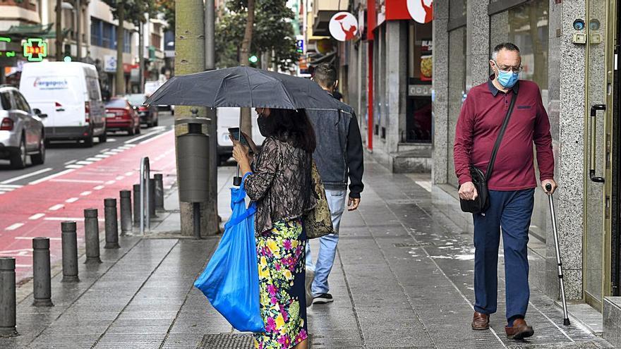 Paseantes bajo la lluvia, ayer, en Las Palmas de Gran Canaria.