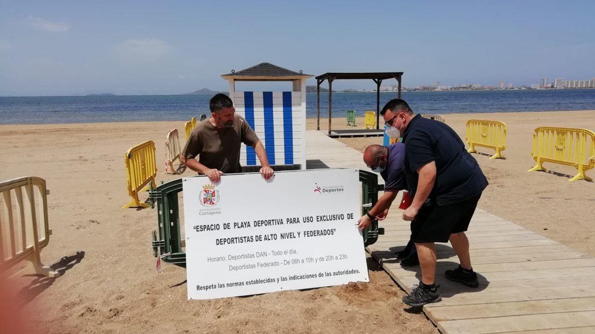 Empleados municipales colocan carteles informativos en una de las playas habilitadas para la práctica de deportes acuáticos, ayer.