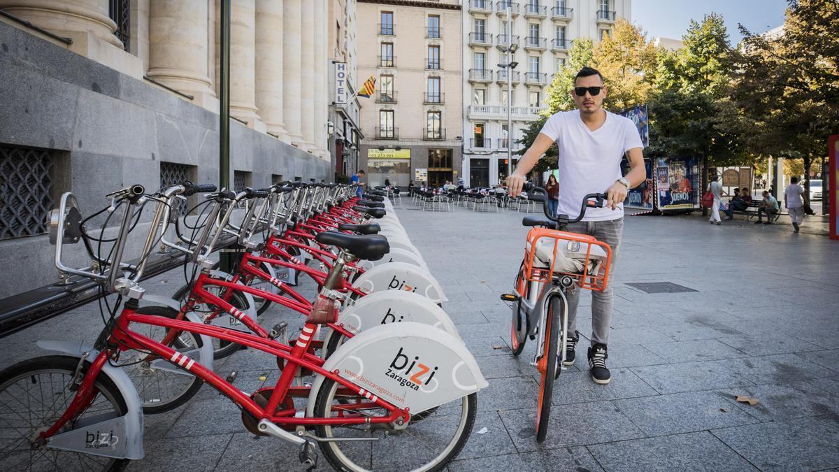 Un usuario con una bicicleta de Mobike pasa junto a la estación Bizi en la plaza España.