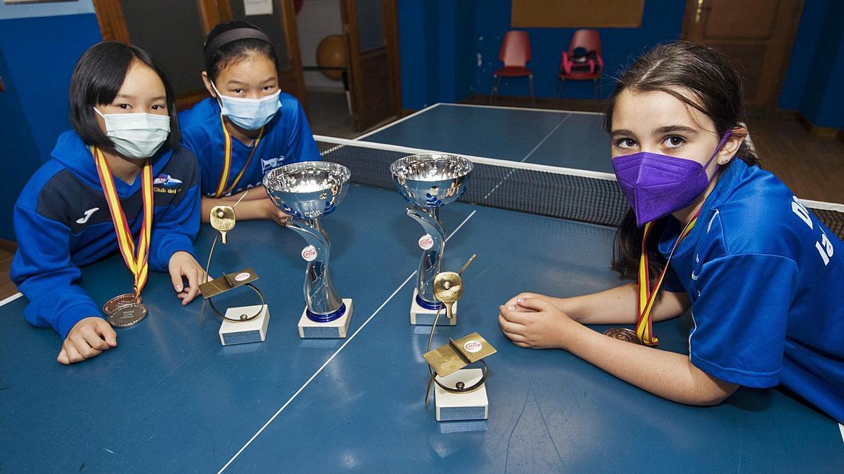 Jiaqi Guo Chen, Miao Chen y Teresa Carrasco, con sus medallas y trofeos, en una tabla de tenis de mesa del Club del Mar.    // CASTELEIRO/ROLLER AGENCIA