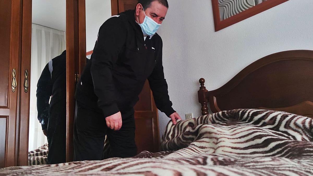 Ramiro Dosantos cubre la cama con una manta, en su casa del barrio San Francisco de Turón. | C. M. B.