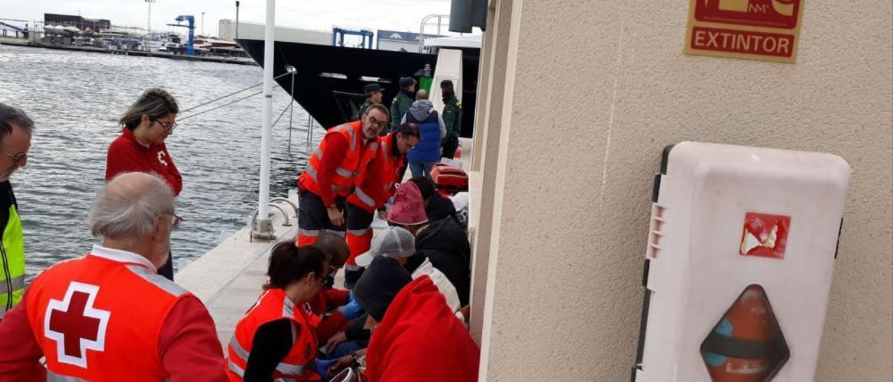 Sanae, de pie con otros voluntarios, atiende a unos inmigrantes llegados a Tabarca.