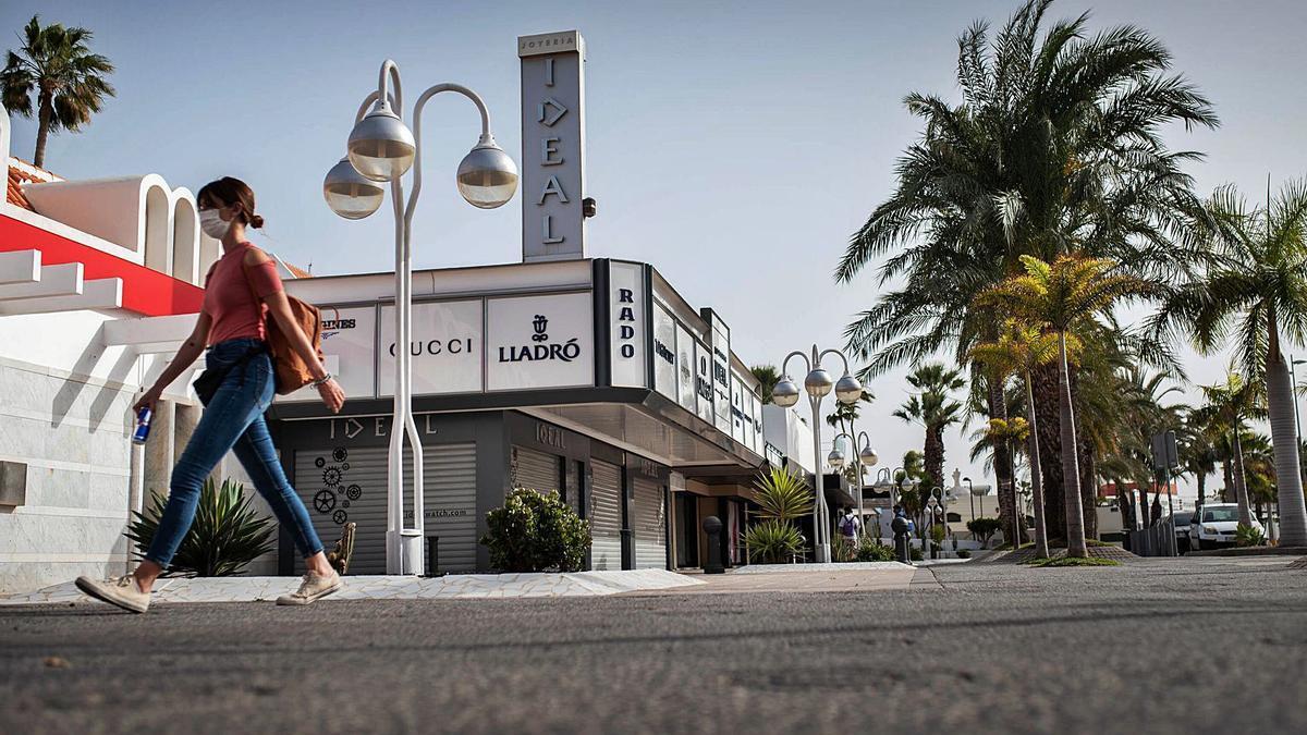 Una mujer pasa ante un centro comercial de primeras marcas, cerrado por la pandemia, en el sur de Tenerife.