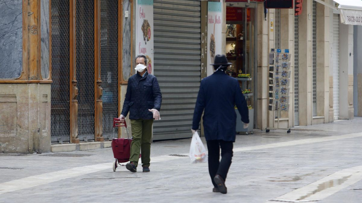 Dos hombres, protegidos con guantes y mascarillas, caminan esta semana por el Centro de Málaga.