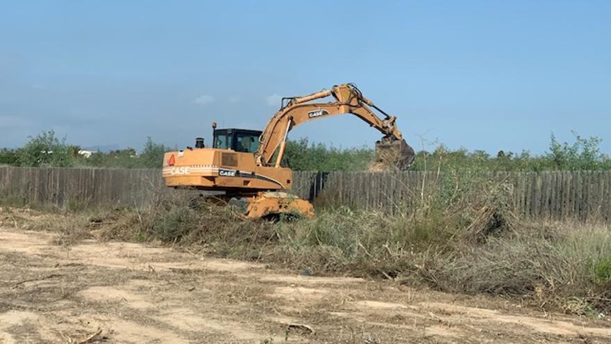 La máquina retro limpia el terreno junto a la carretera del campico y luego vierte la maleza y los residuos dentro del recinto del parque botánico en Rojales