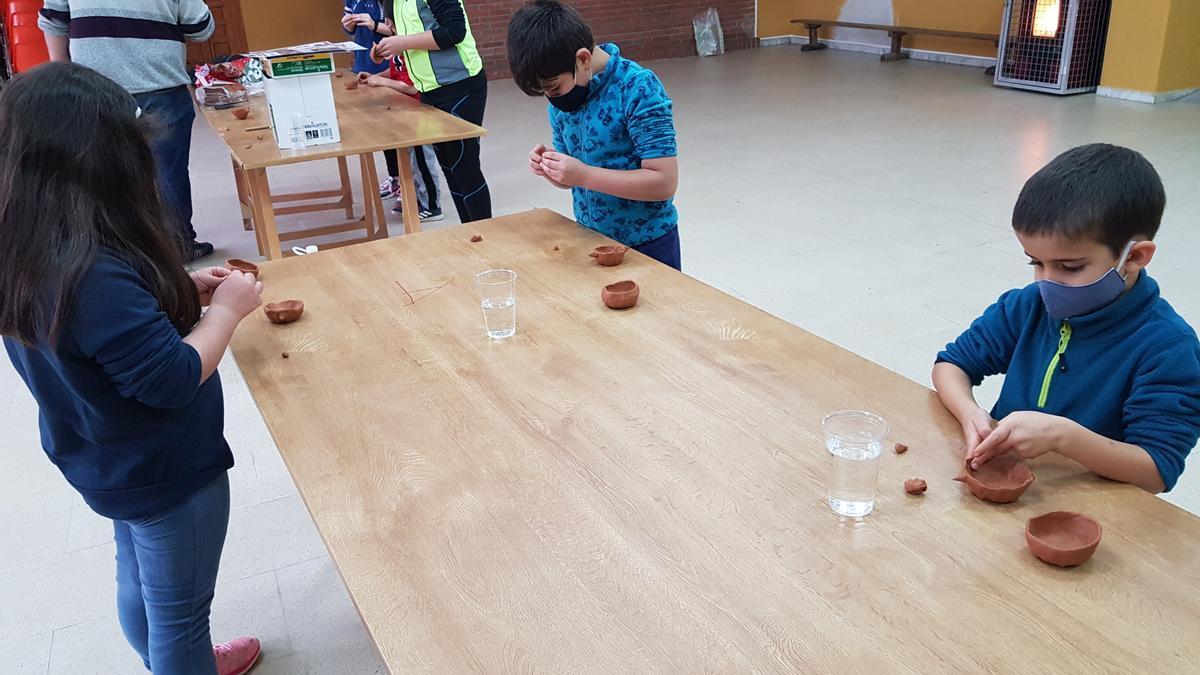 Niños participando en un taller de artesanía con arcilla.