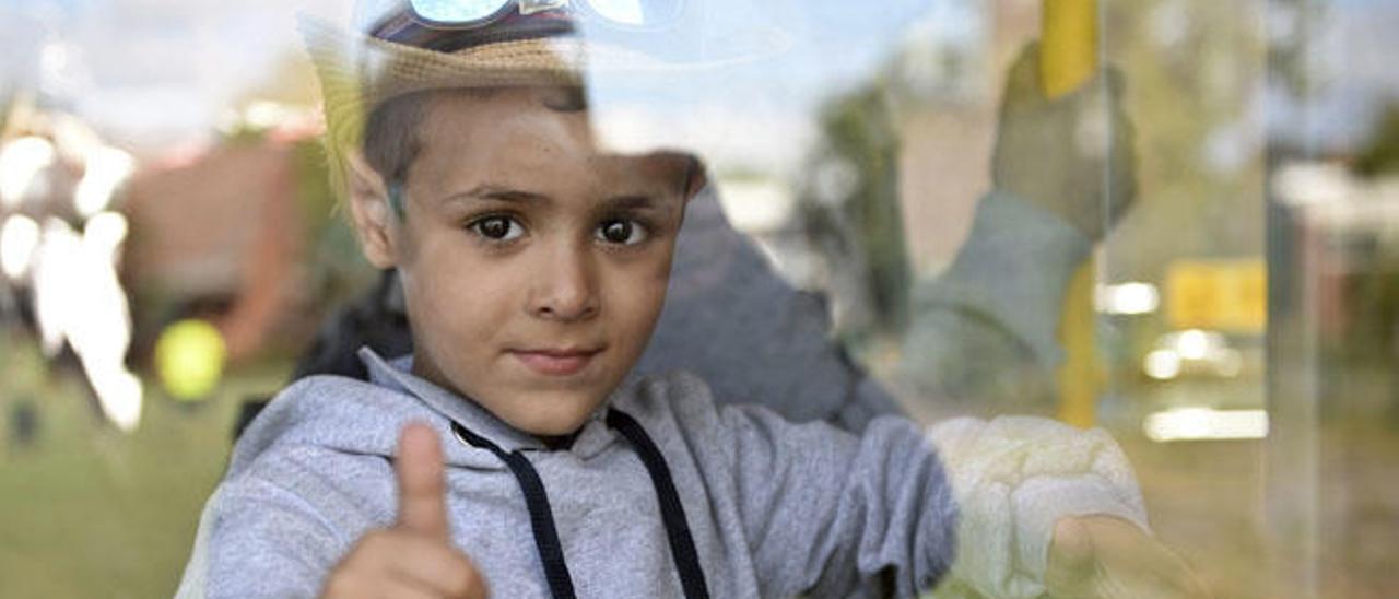 Un niño refugiado saluda mientras espera salir de una guagua ayer en Berlín.